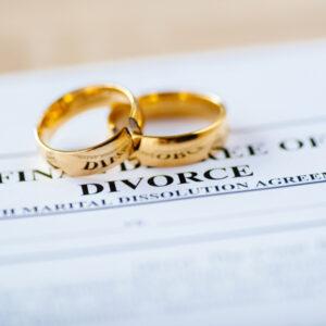 two broken golden wedding rings on divorce papers
